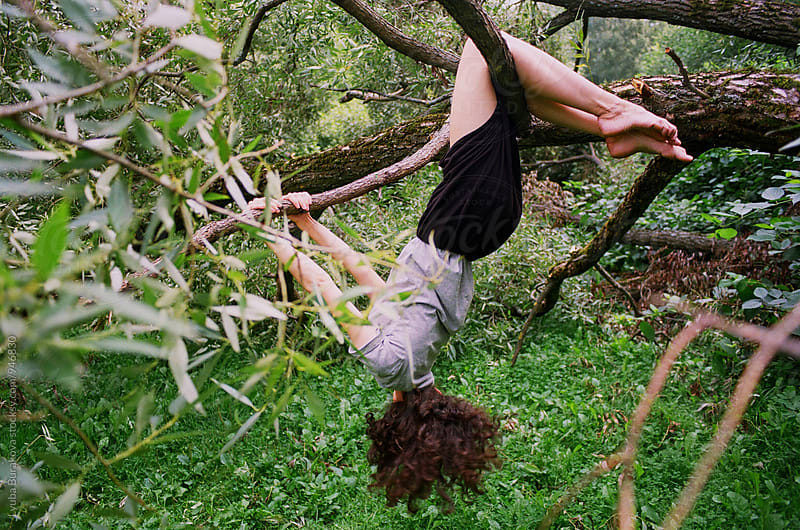 Curly girl hands on a tree upside down by Lyuba Burakova for Stocksy United