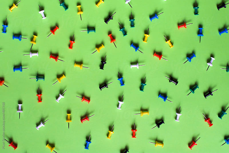 Colorful pins on green background by Pixel Stories for Stocksy United
