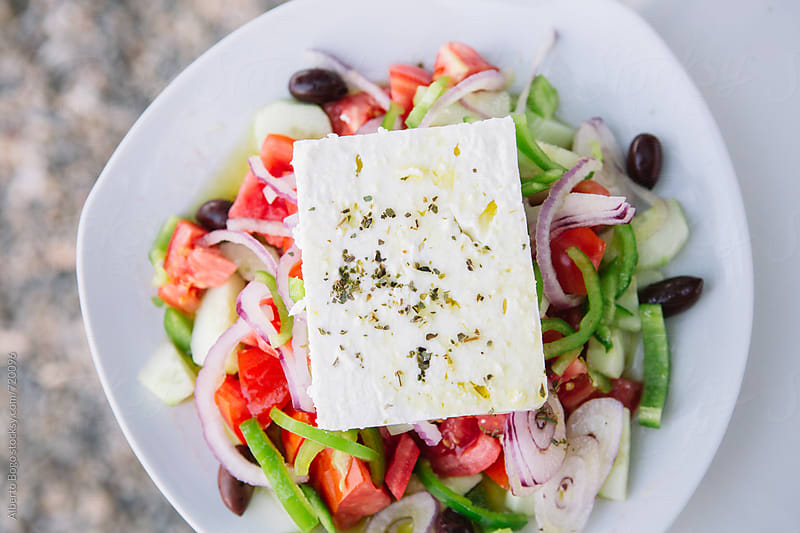 Fresh greek salad on white plate by Alberto Bogo for Stocksy United