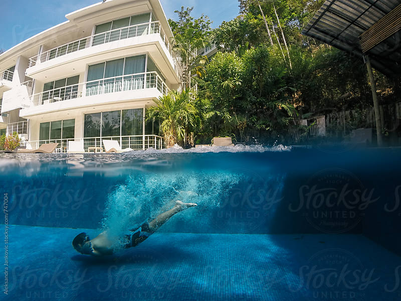 Man Swimming Underwater in the Pool at the Tropical Resort by Aleksandra Jankovic for Stocksy United
