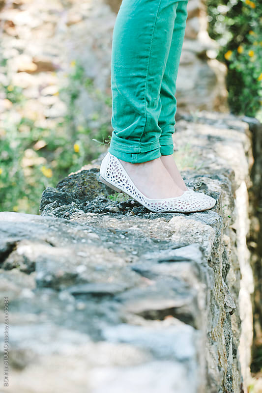 Detail of the feet of a girl on a stone wall of a park. by BONNINSTUDIO for Stocksy United
