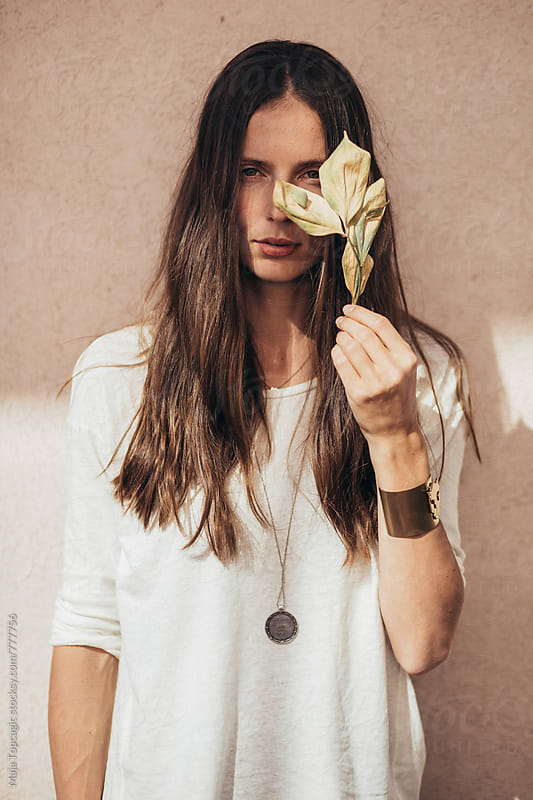 Portrait of a beautiful woman with no make up holding a leaf by Maja Topcagic for Stocksy United