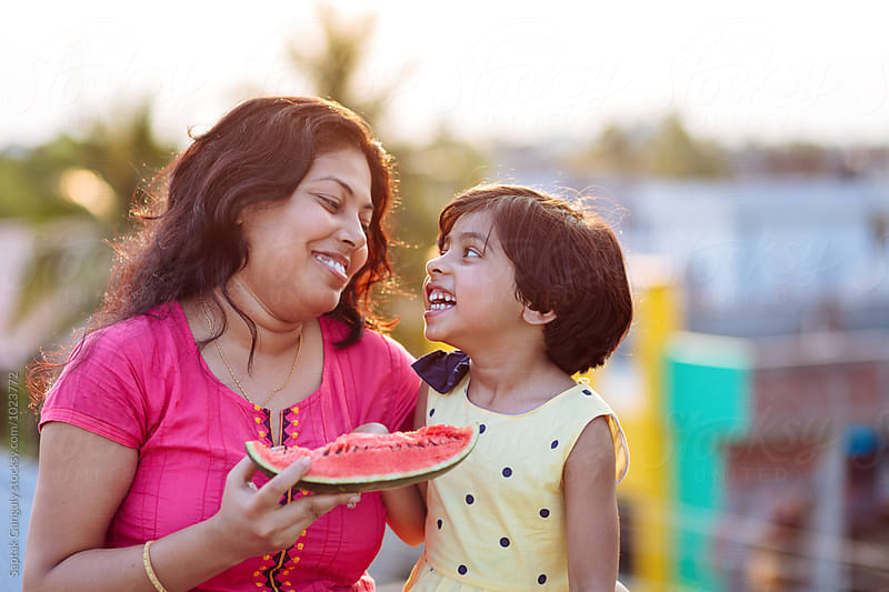 Mother and daughter sharing a cheerful moment while eating watermelon by Saptak Ganguly for Stocksy United