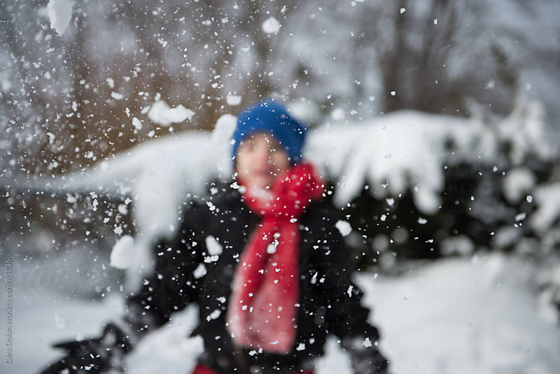Child wearing winter gear happily throws snow into the air by Cara Dolan for Stocksy United