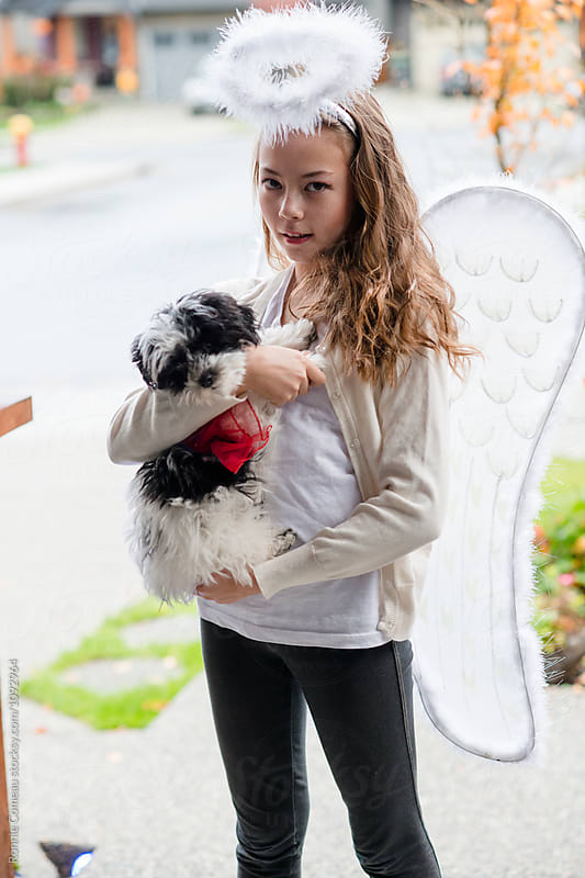 Angel Girl and Super Dog on Halloween by Ronnie Comeau for Stocksy United