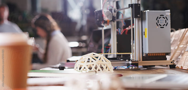Desk at busy 3D printer business by Aila Images for Stocksy United