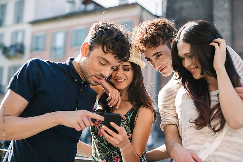 Group Of Friends Using A Cell Phone In The City By Gic