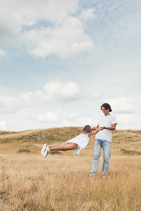 Teenage boy spinning little girl around in a field on a summer day by Cindy Prins for Stocksy United