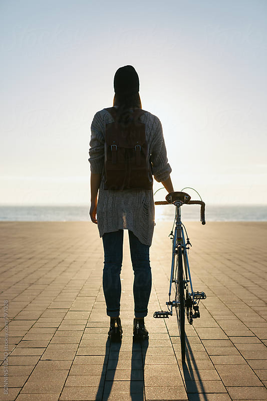 Back view of a woman with her vintage bicycle looking the sea. by BONNINSTUDIO for Stocksy United