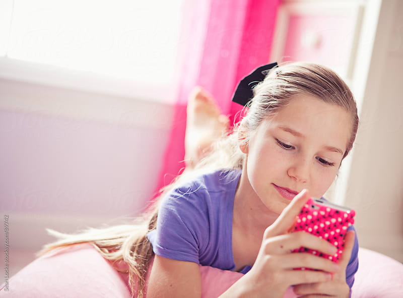 Girl: Cute Girl Reads Text Messages on Cell Phone by Sean Locke for Stocksy United