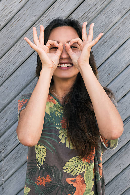 Asian woman with ok gesture on eyes by Danil Nevsky for Stocksy United