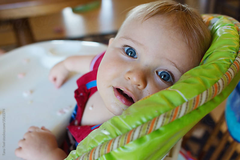 toddler sits in highchair looking at camera by Tana Teel for Stocksy United