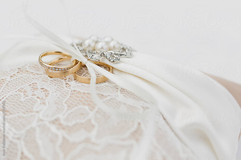 Lace fabric with gold and silver wedding rings by Amir Kaljikovic for Stocksy United
