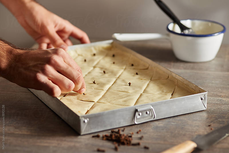 Man decorating cut uncooked baklava with cloves by Martí Sans for Stocksy United