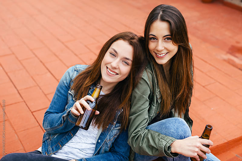 Two young women having fun and drinking beer sitting on the floor. by BONNINSTUDIO for Stocksy United