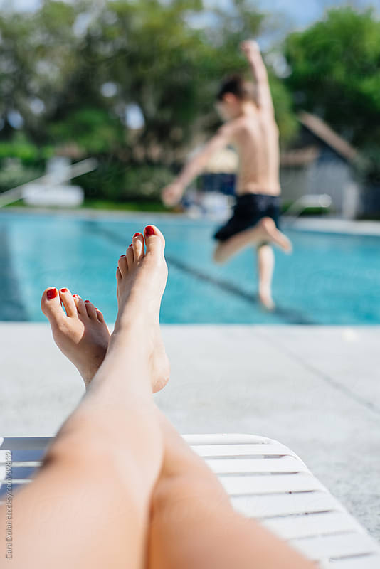 Mother relaxes poolside as her son leaps into the water by Cara Slifka for Stocksy United