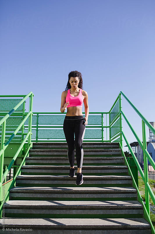 Fit woman running down the stairs by michela ravasio for Stocksy United