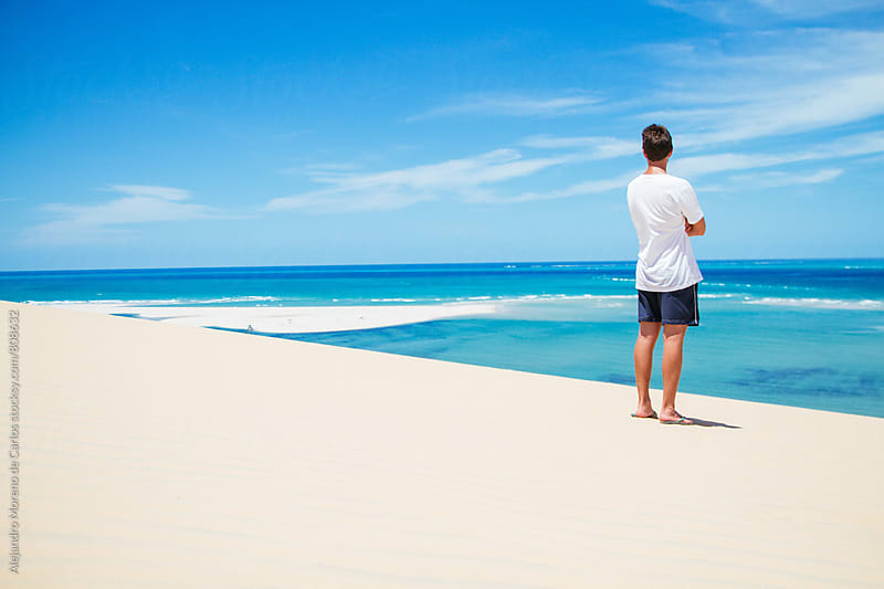Man in shorts standing on a white sandy beach looking at the turquoise clear waters of the ocean by Alejandro Moreno de Carlos for Stocksy United
