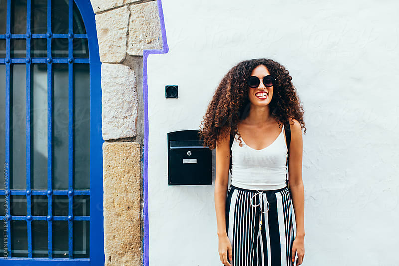 Smiling alone tourist visiting a beautiful village.  by BONNINSTUDIO for Stocksy United