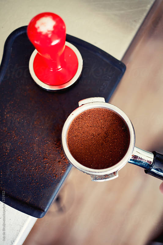 A close up of a coffee piston filled with freshly grinded coffee before preparing an espresso by Ivo de Bruijn for Stocksy United