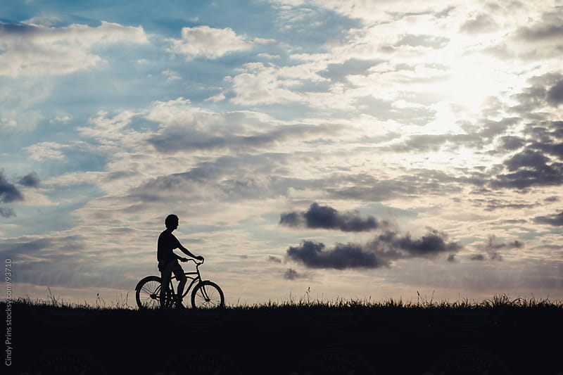 Silhouette of a teenage boy on a bicycle getting ready to go for a ride by Cindy Prins for Stocksy United