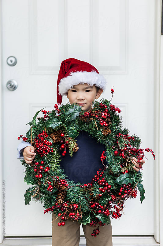 Asian boy holding a wreath celebrating Christmas by Suprijono Suharjoto for Stocksy United