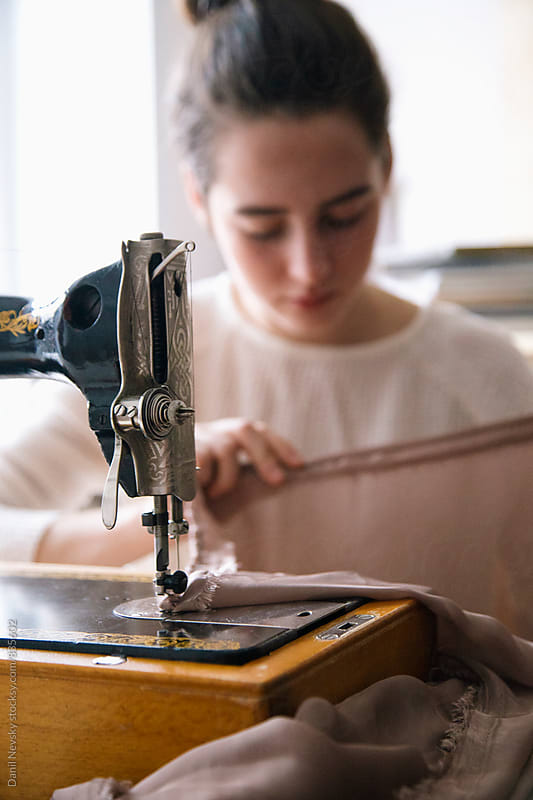 Young woman working with vintage sewing machine by T-REX & Flower for Stocksy United