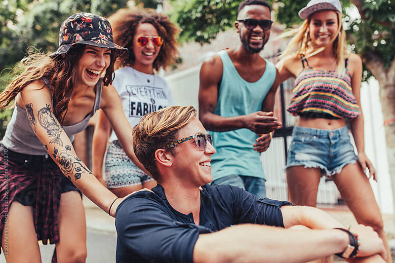 Group of teenage friends having fun on the city street by Jacob Lund for Stocksy United