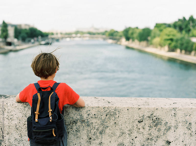 Rear view of boy looking out over the Seine, Paris by Kirstin Mckee for Stocksy United