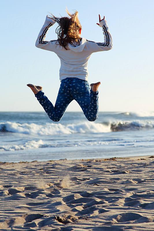 Happy girl jumping at the beach by Carolyn Lagattuta for Stocksy United