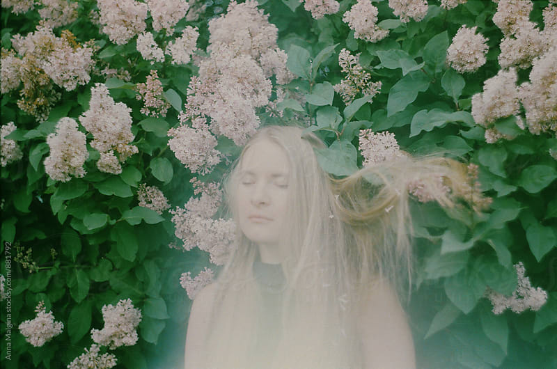 A film portrait of a blond woman in the lilac bush  by Anna Malgina for Stocksy United
