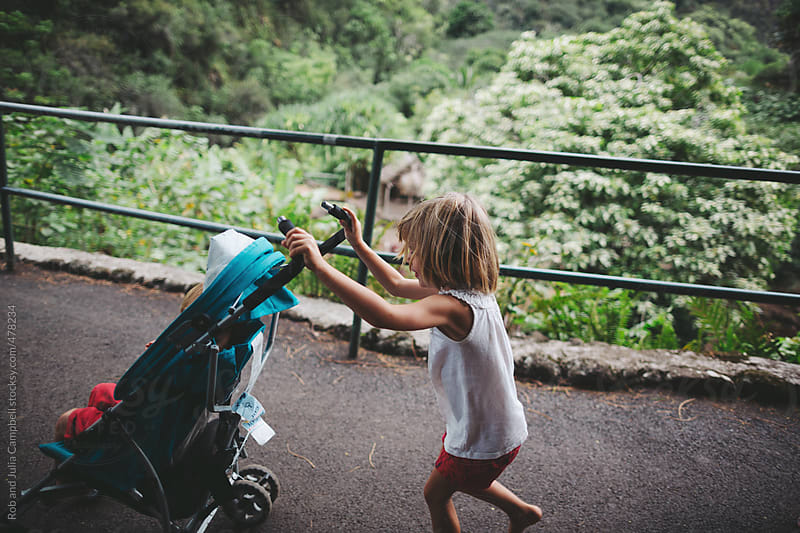 Cute young girl helping push stroller on nature path by Rob and Julia Campbell for Stocksy United