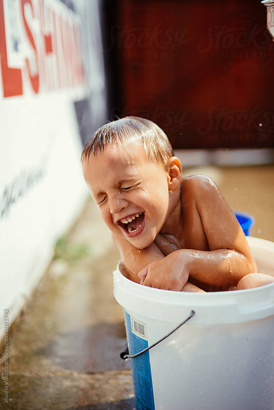 Boy is playing with the water by Jovana Vukotic for Stocksy United
