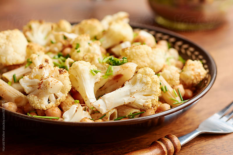 Spicy Roasted Cauliflower And Chickpeas on Penne Pasta by Harald Walker for Stocksy United