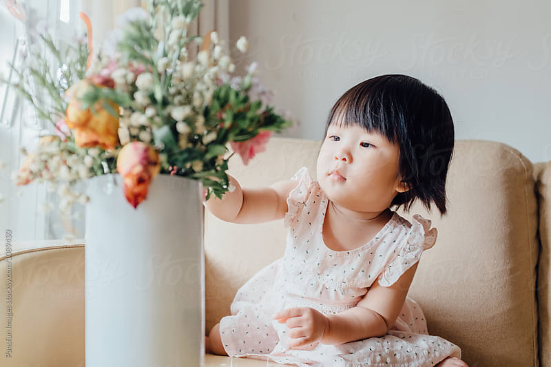 Asian baby girl with flower by Xunbin Pan for Stocksy United