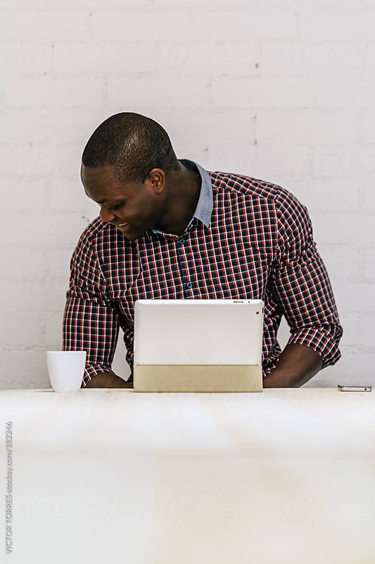 Black Man with a Digital Tablet on a Wooden Table by VICTOR TORRES for Stocksy United