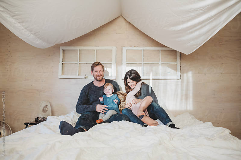 Trendy young family hugging together inside on white bed in winter - candid by Rob and Julia Campbell for Stocksy United