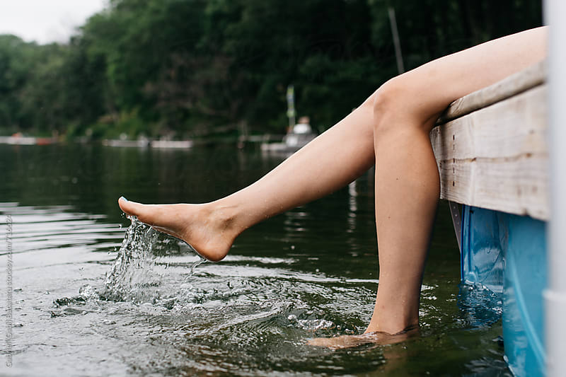 Woman sitting on a pontoon and splashing the water with her legs by Gabriel (Gabi) Bucataru for Stocksy United