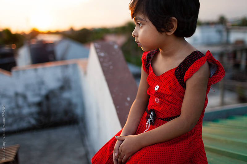 Little girl sitting on rooftop at sunset in a pensive mood by Saptak Ganguly for Stocksy United