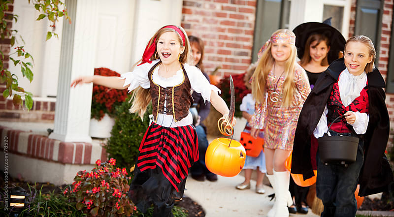 Halloween: Kids Running to Next House for Candy by Sean Locke for Stocksy United