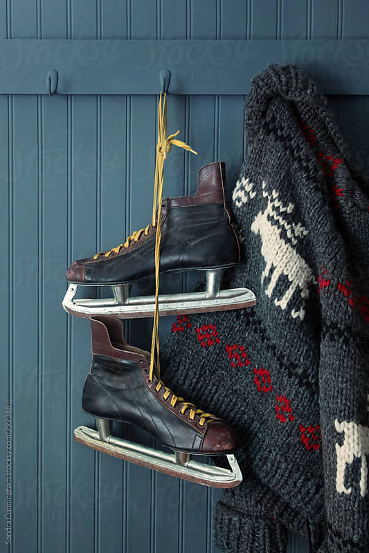 Men's vintage skates  and sweater hanging on hooks by Sandra Cunningham for Stocksy United