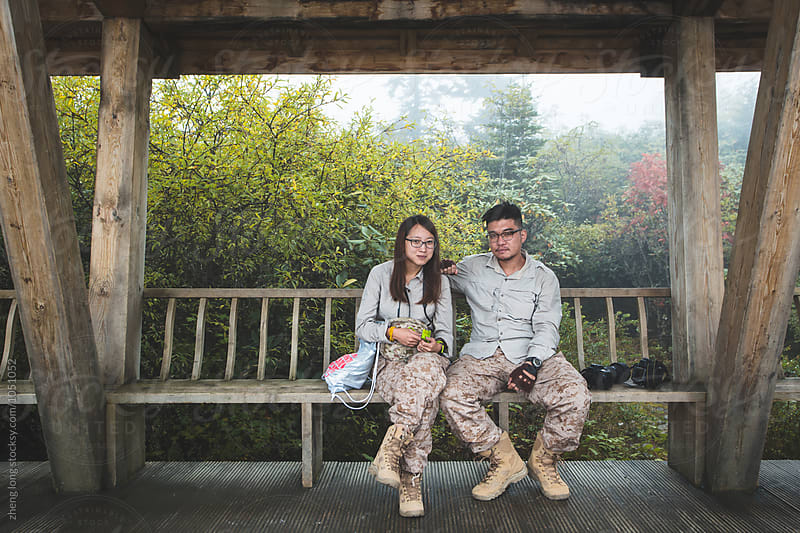 Young couple sitting on the bench by zheng long for Stocksy United
