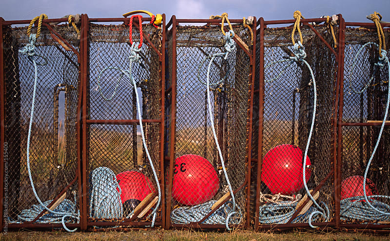A row of king crab pots with buoys and lines by Mihael Blikshteyn for Stocksy United