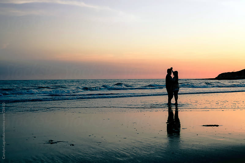 Silhouette of a couple embracing at sunset on the beach in Santa Cruz by Carolyn Lagattuta for Stocksy United