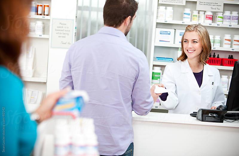 Pharmacy: Customer Hands Prescription to Pharmacist by Sean Locke for Stocksy United
