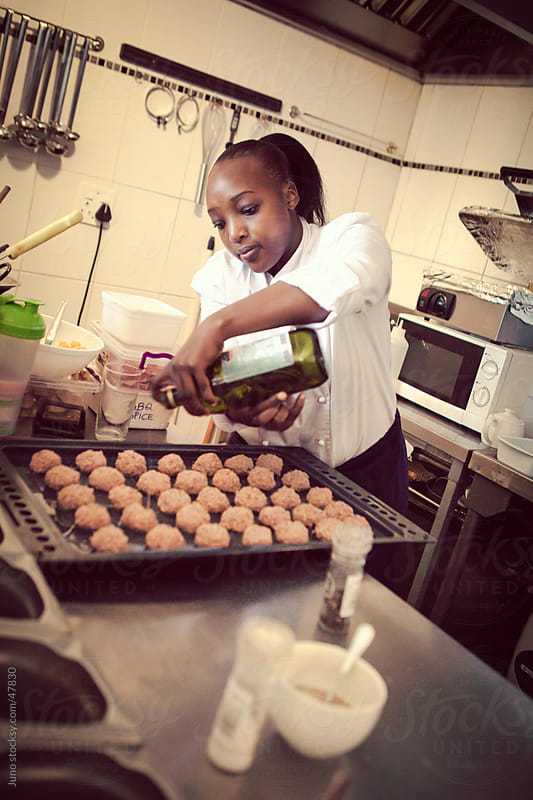 Female African cook baking in a restaurant by Micky Wiswedel for Stocksy United