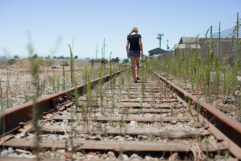 Young girl walking along the railroad tracks by Carolyn Lagattuta for Stocksy United
