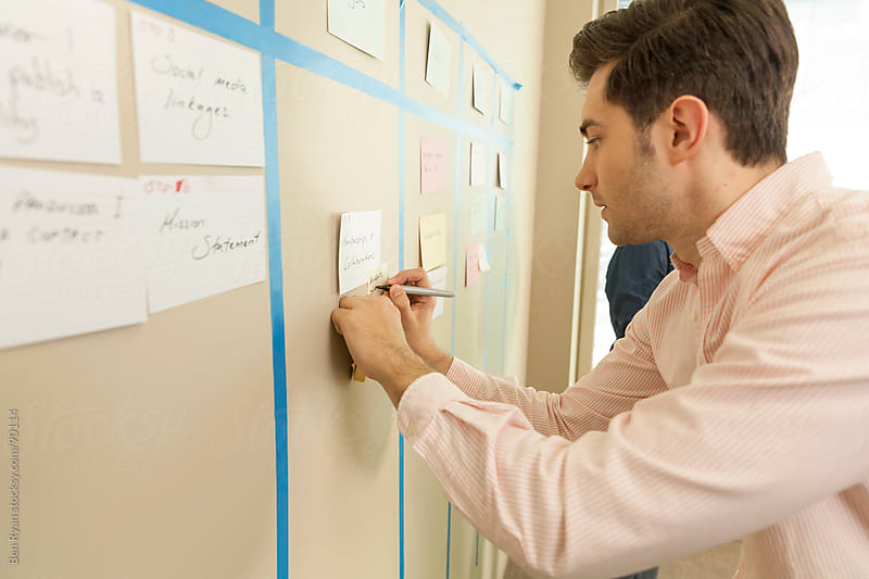 Agile software team member writing on the iteration card wall by Ben Ryan for Stocksy United