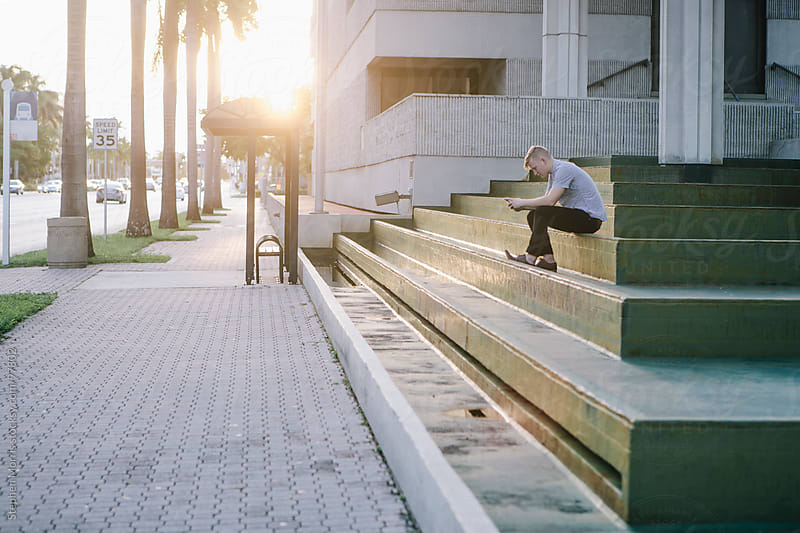 Young Man Sitting on Steps by Stephen Morris for Stocksy United