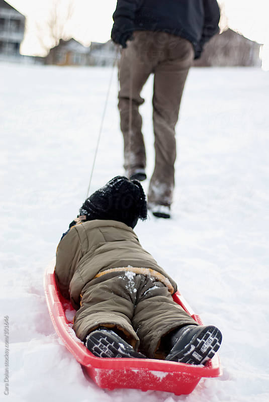 Father pulls his son in a sled up a snowy hill by Cara Dolan for Stocksy United